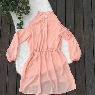 Superfin aprikosfärgad klänning i storlek 38. Öppen i ryggen (andra bilden). Frakt ingår i priset.