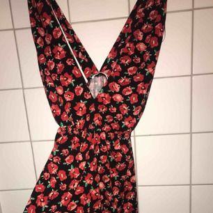 Playsuit från pullandbear i svart tyg med röda rosor. Aldrig använd. Supergullig med en vit t-shirt under. Storlek S. Kan fixa bättre bilder. Köparen står för frakt.