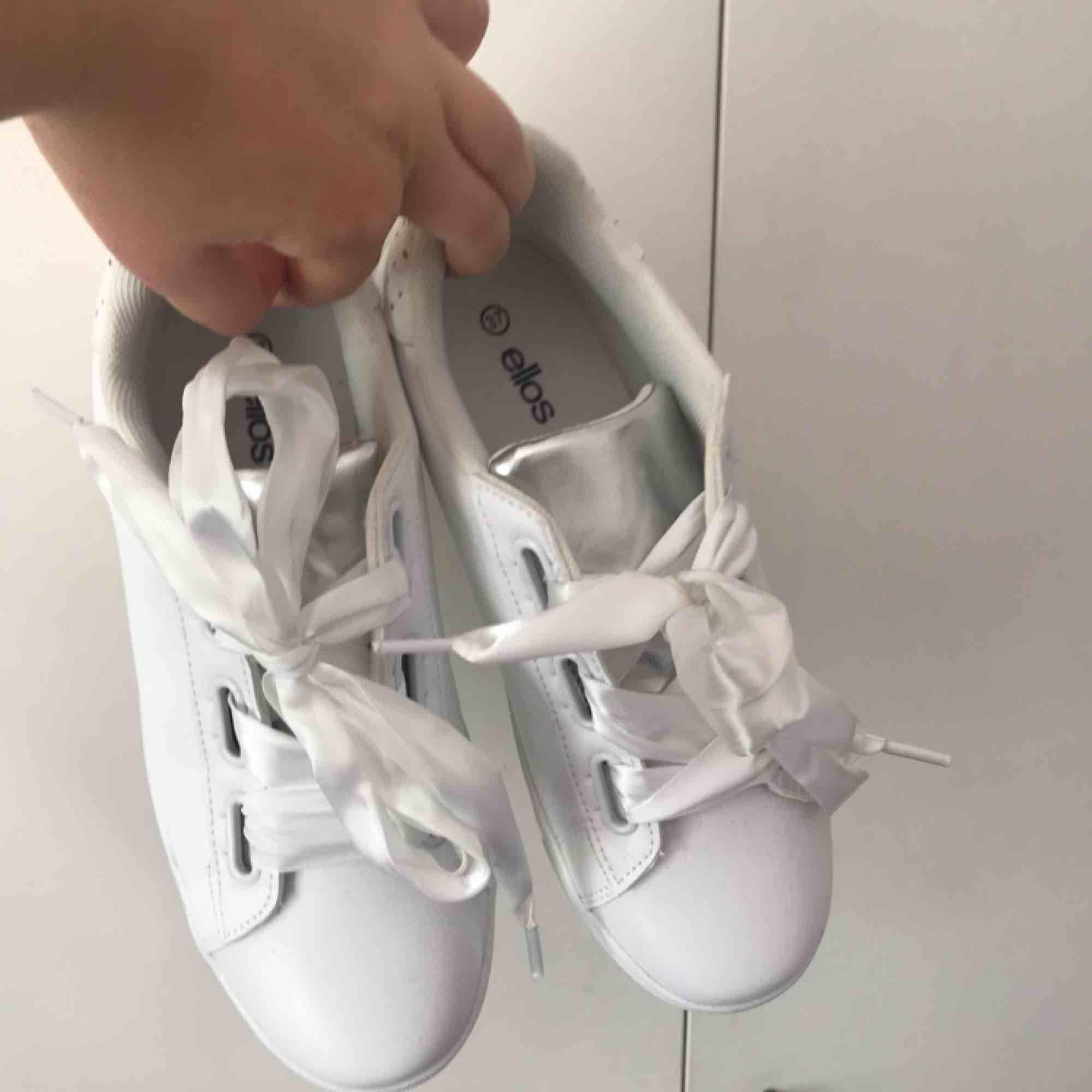 Vita sneakers med silkesband som skosnöre. Från Ellos egna märke. Passar mig som har 38. Aldrig använda. 150 + frakt. Kan mötas upp i tranåsområdet eller i sthlm.. Skor.