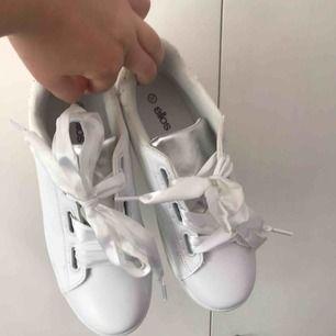 Vita sneakers med silkesband som skosnöre. Från Ellos egna märke. Passar mig som har 38. Aldrig använda. 150 + frakt. Kan mötas upp i tranåsområdet eller i sthlm.