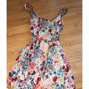 Jättefin blommig klänning ifrån Bershka med detaljer i ryggen