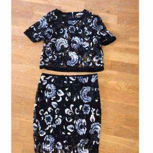 Jättefint set ifrån Gina Tricot i silver svart och blått material. T-shirt och kjol till. Använd 1 gång.