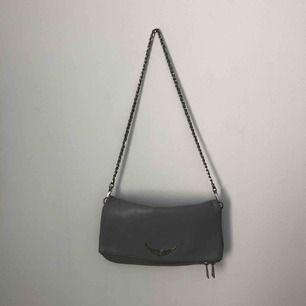 En fin, grå Zadig & Voltaire väska i använt skick. Det långa bandet saknas.  Nytt pris: 2700kr