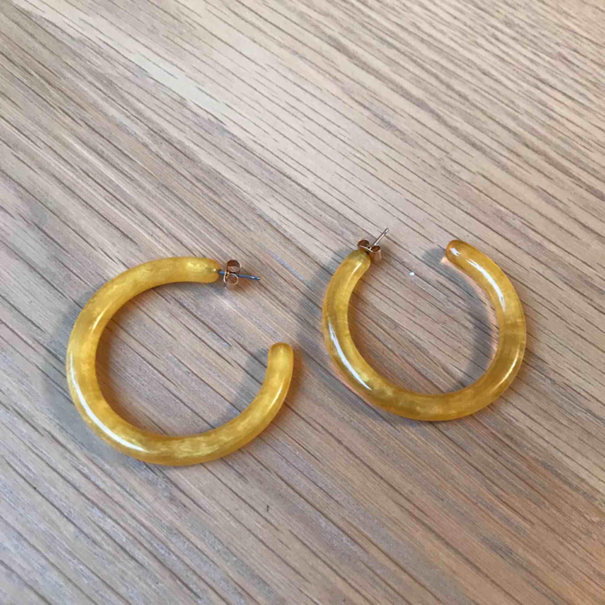 Roliga gula örhängen från H&M, använda kanske en gång max. Går att hämta på Södermalm annars tillkommer frakt på 10 kr. Accessoarer.