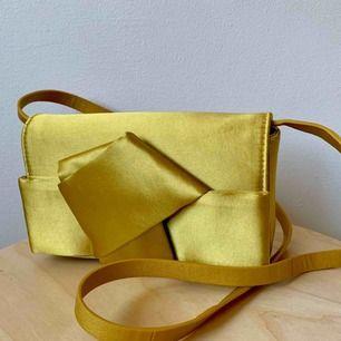 Väska gul siden väska som aldrig kommit till användning. Mått: 20 cm bred, 12 cm hög, 4 cm djup. Kan hämtas på söder, annars fraktar jag gärna för 40 kr