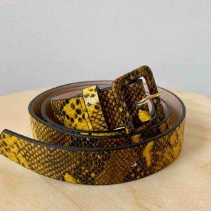 Skärp i gult ormskinnsprint - helt nytt! Aldrig kommit tillanvändning men så fint ✨ Mått: 83 cm - 93 cm (innersta hålet - yttersta hålet) Går att hämta på söder, annars kostar frakt 40 kr