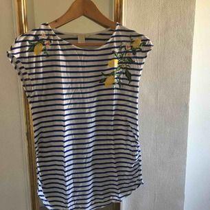 Söt, blåvit-randig tröja från H&M! På tröjan finns flera broderade citroner och små blommor. Den är i strl XS och har inte använts så mycket. Köparen står för frakt 🥰