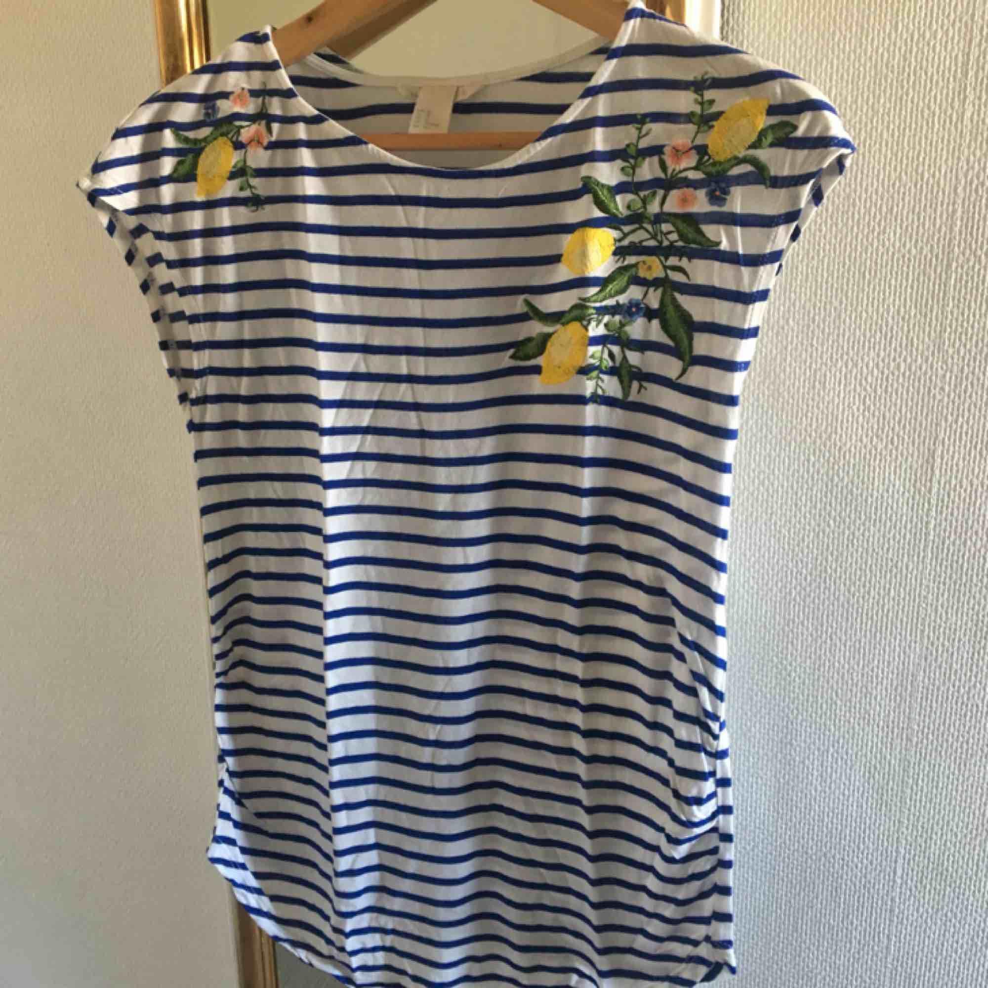 Söt, blåvit-randig tröja från H&M! På tröjan finns flera broderade citroner och små blommor. Den är i strl XS och har inte använts så mycket. Köparen står för frakt 🥰. Toppar.