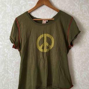 Retro grön t-shirt. Detaljer i form av röda sömmar och peacemotiv. Står XL i den, men passar bra på en M. Kan frakta eller mötas upp I Stockholmsområdet.