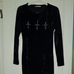 En sammets klänning i strl XS med tre diamant kors på bröstet, ganska stretchig skulle nog också passa S!