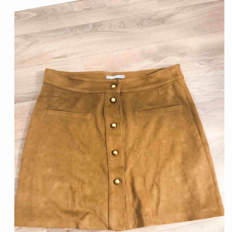 """Brun """"mocka""""kjol ifrån Gina Tricot med guldknappar. Superfin och fint skick. Säljes pga fel storlek. . Kjolar."""