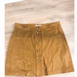 """Brun """"mocka""""kjol ifrån Gina Tricot med guldknappar. Superfin och fint skick. Säljes pga fel storlek."""