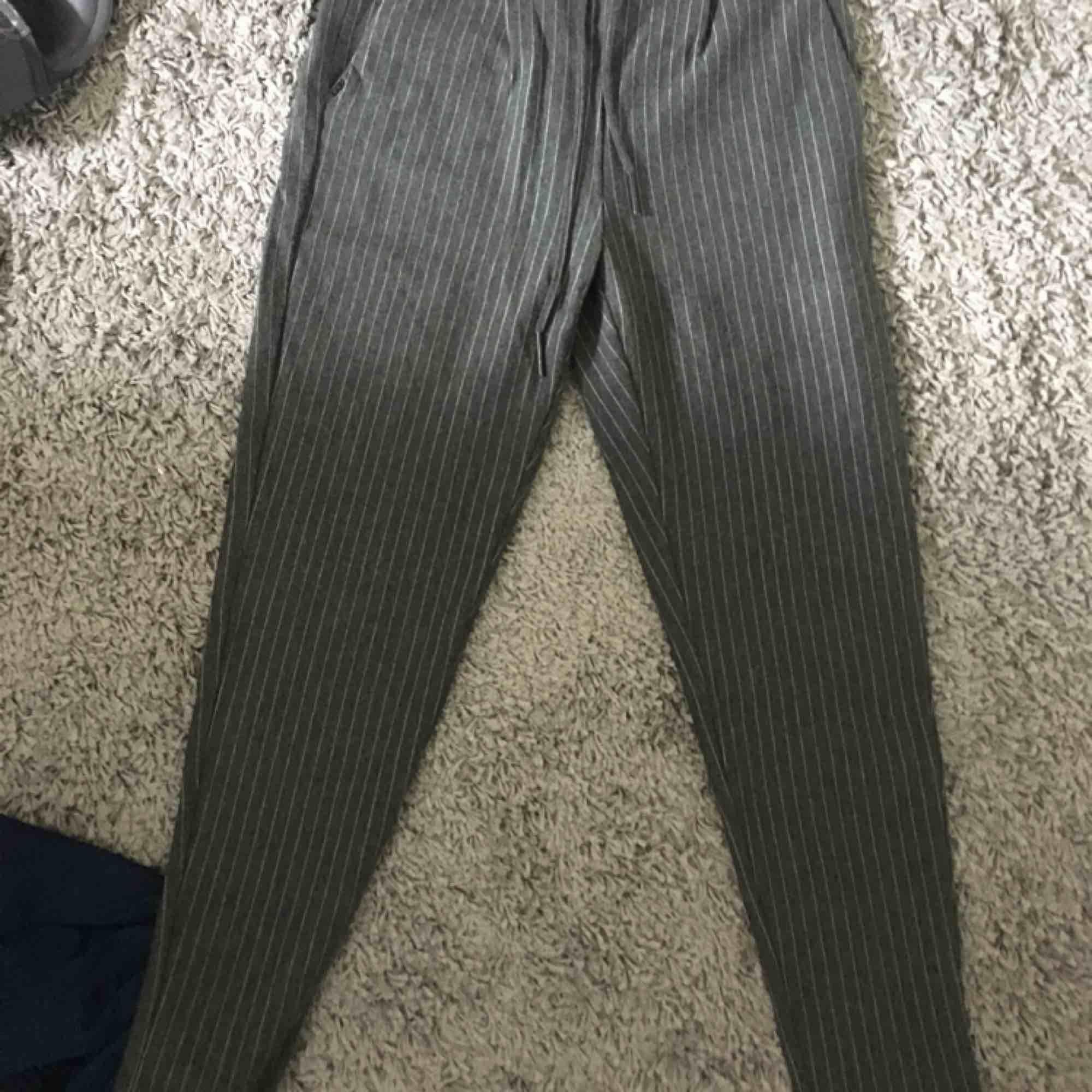 Snygga kostymbyxor i mjukt material från Holmlunds. Finns snörning i midjan, samt att man kan sätta i ett skärp i dom om man vill. Används ej längre av mig så säljer vidare☺️. Jeans & Byxor.