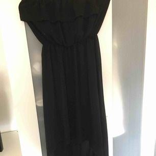Svart klänning från Spanien, off shoulders. Är lite längre baktill och kortare framtill vid benen.