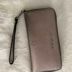 Äkta Michael kors plånbok med plats för kort, pengar och mobiltelefon. Använd och tappat lite färg därav det billiga priset.