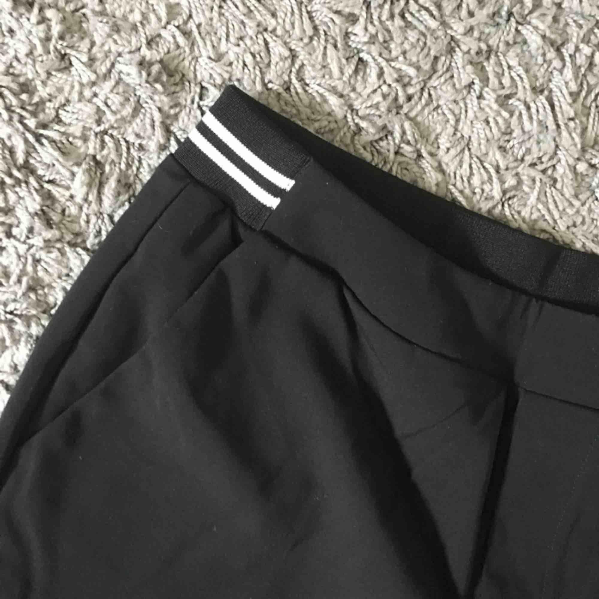 Svarta Kostymbyxor med resår baktill, vita streck som detalj i midjan där bak. . Jeans & Byxor.