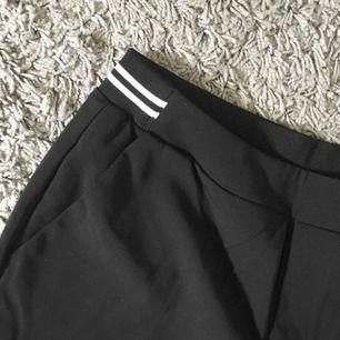 Svarta Kostymbyxor med resår baktill, vita streck som detalj i midjan där bak.