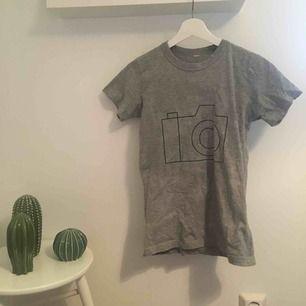 En grå t-shirt med ett tryck i form av en enkel designad kamera. Fick den för typ tre år sedan och vet inte vilket märke det är. Frakt tillkommer