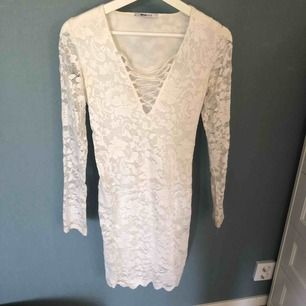 Vit klänning i spets med knytning i fram och långa spets armar använd 1 gång till speciellt event, finns insydd inneklänning så minns den inte som genomskinlig🥰