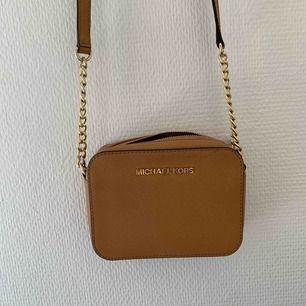 Ljusbrun Michael Kors väska i gott skick, använt fåtal gånger men tyvärr fått ett litet märke av en penna uppe på höger sidan av väskan.