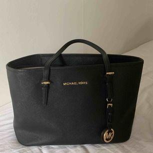 En svart väska från Michael Kors i en mindre modell men fortfarande mycket rymlig.