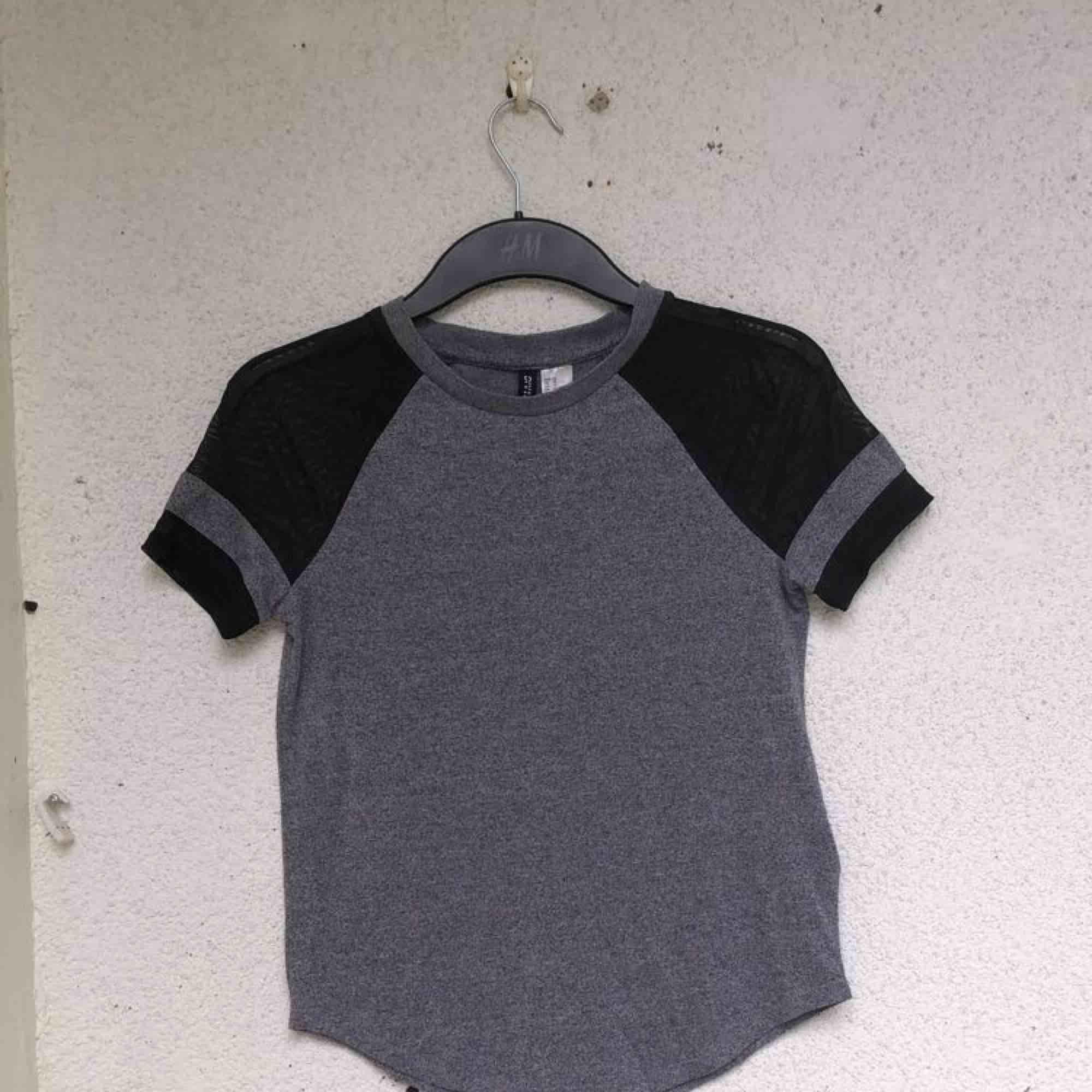 Grå T-shirt med svarta genomskinliga detaljer på armarna. Använd fåtal gånger och är i väldigt bra skick. Frakt ingår i priset.   . T-shirts.