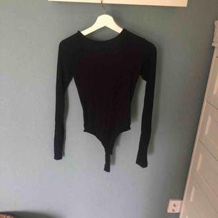Långärmad svart body med öppen rygg från bik bok, lite fläck på ryggen men inget man tänker på