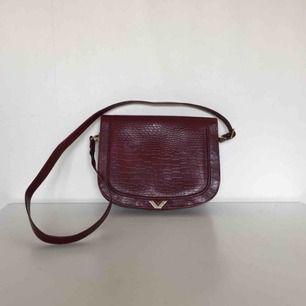 Vinröd handväska! Köpt second hand och har knappt använt den sedan dess, jättefint skick. Praktisk med två stora och två små fack (bild 3)