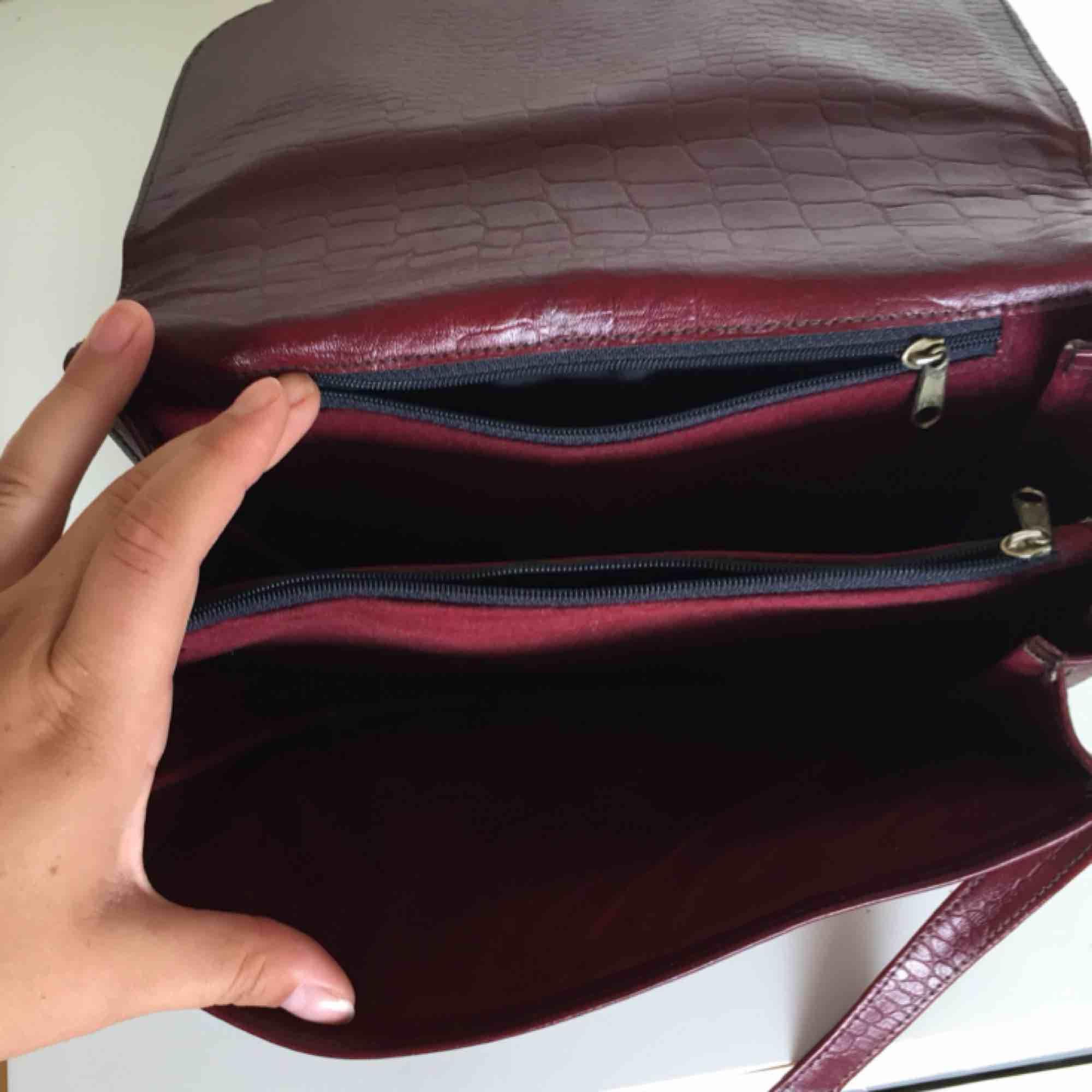 Vinröd handväska! Köpt second hand och har knappt använt den sedan dess, jättefint skick. Praktisk med två stora och två små fack (bild 3). Väskor.
