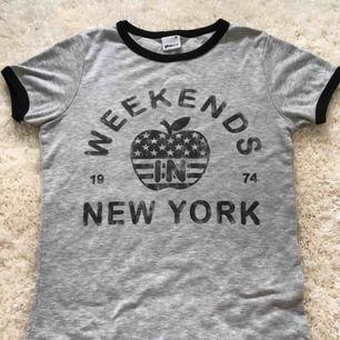 En grå tshirt med tryck och svarta kanter från ginatricot i storlek XS. Knappt använd och säljer för att det inte är min stil. Kan mötas i Stockholm :)