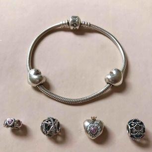 Äkta Pandora armband med två stopp och fyra berlocker. Om du bara vill köpa berlockerna eller bara armbandet kan vi diskutera ett pris.