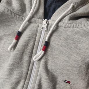 En till Tommy Hilfiger hoodie, denna är grå, är i ett tjockare material och har en zipper🥰 den är i M i herrstorlekar, men funkar på alla kön såklart🙌 frakt tillkommer