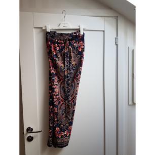 Marinblå mönstrade byxor med skärp i midjan. Hög midja.