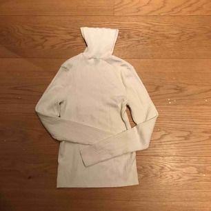 Långärmad vit polotröja. Ribbat och töjbart material.