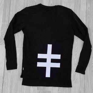 Svart lång herr sweatshirt från Jack&Jones Core i modellen regular fit storlek M i fint skick förutom minimala sprickor i trycket. Har en ficka fram. Nypris 79€, ca 832kr. Obs ryggen som visas på första bild.
