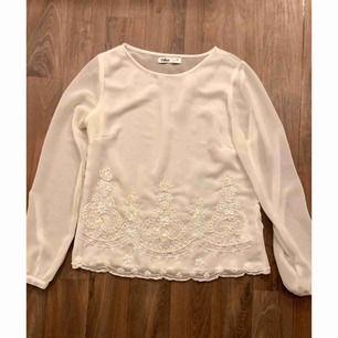 Superfin vit tröja i fint material med brodyrdetaljer i pärlor. Superfint skick använd 1 gång.