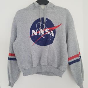 En jättemysig grå hoodie med stort NASA tryck på framsidan och 2 ränder på vardera ärm och lite croppad! Köpt på H&M i storlek M men passar toppen på mig som är en S. Använd varsamt och har inga skador! Säljs pågrund av att det inge är min stil. Köparen står för frakten!🌻