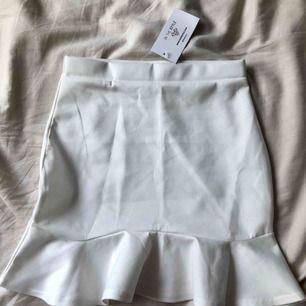 Vit kjol med volangkant från In The Style. Sitter sååå fint men den är tyvärr lite för tight för mig. Helt oanvänd med prislappen kvar. Frakt tillkommer.