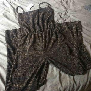 Jumpsuit i glitter guld/svart. Har aldrig blivit använd, därav är lapparna kvar. Fraktkostnad tillkommer på 35kr.