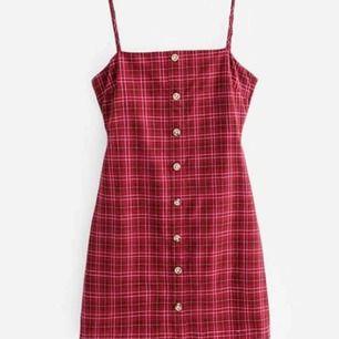 Fin rutig klänning med smala band och knyt där bak som är köpt utomlands. Den är tyvärr för liten för mig och därför säljer jag den. Helt oanvänd men prislappen har lossnat. Frakt tillkommer.