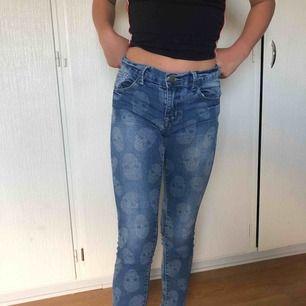 Blåa Jeans med ljusgråa skallar på. Lågmidjade, nyskick. Nypris är 149kr, frakt tillkommer också.