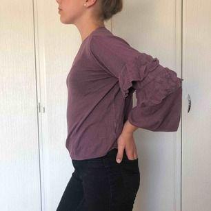 Smuts-lila tröja med volanger på ärmarna. M men krympt i tvätten så den skulle nog passa en S bättre.  Nypris 129kr Frakt tillkommer