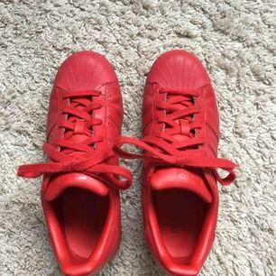 Ett par röda Superstars från Adidas. Är ganska svåra att få tag på. Använda några gånger men inget som syns. Så gott som nya! Frakten ingår!
