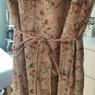 Långklänning med knäppning bak och slits.