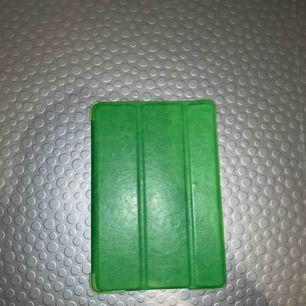 Ett grönt iPad mini skal och man kan ställa upp ipaden när man kollar på film osv. Helt oanvänt :)
