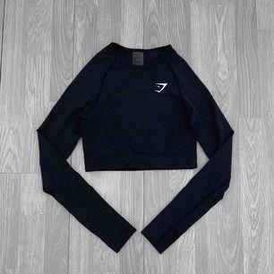 """Äkta Gymshark vital seamless long sleeve tröja i en kortare modell.  Knappt använd i färgen """"black marl"""" Storlek S.  Frakt kostar 36kr extra, postar med videobevis/bildbevis. Jag garanterar en snabb pålitlig affär!✨ ✖️Fraktar endast✖️"""