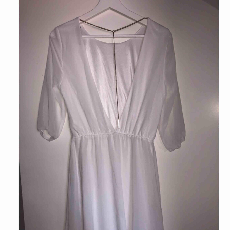 Underbar vit klänning med kedjedetalj i ryggen. Kedjan är guldfärgad. Använd 1 gång.. Klänningar.