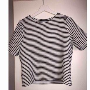 """T-shirt i """"tjockare"""" finare material. Svart och vitrandig. Bra skick."""