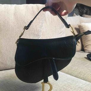 Finaste Dior Saddle bag (kopia) som jag köpt på en resa för 2700kr. Använt ett par gånger så den är fortfarande i grymt bra skick! Spårbar frakt på 63kr tillkommer!