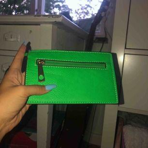En limegrön clutch som passar perfekt för att ha en mobil och korthållare